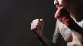 Muay Thai boxing, strong tattooed male training before fight in gym, slow-motion. Stock footage stock video