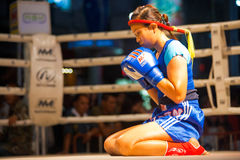 Muay Thai Female Alone Wai Khru. BANGKOK, THAILAND - DECEMBER 8, 2010: An unidentified female muay thai fighter reflects in a kickboxing ritual called the wai Royalty Free Stock Photos