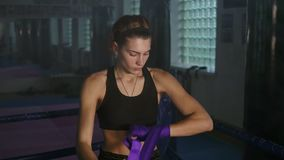 Muay thai female boxer wrapping purple bandages on her hands before fight in dark room with smoke.  stock video footage