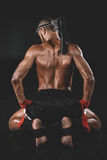 Muay thai fighter sitting on floor isolated on black royalty free stock images