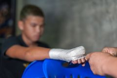 Muay thai fighter swathing hand in boxing bandage. Coaches preparing and wrapping muay thai fighter hand with traditional hemp clothnPhoto Taken On: April 5th stock photos