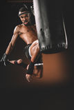 Muay thai fighter training with punching bag, action sport concept Royalty Free Stock Image