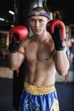 Muay Thaise vechter die zich met handen op rode handschoenen bij gymnastiek bevinden stock afbeeldingen