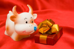 Mucca e un regalo su un colore rosso Immagini Stock