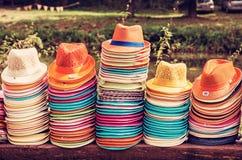 Mucchi dei cappelli di estate in negozio, filtro rosso Immagini Stock