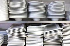 Mucchi dei piatti e dei piatti bianchi in un ristorante Immagine Stock