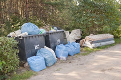 Mucchi dei rifiuti domestici e dell'immondizia in foresta Immagine Stock