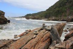 Mucchi della roccia del cairn alla foce fotografie stock