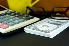 Mucchi delle banconote del dollaro americano e del calcolatore finanziario sulla f nera Immagine Stock