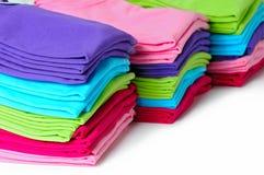 Mucchi delle magliette di donne colorate multi su fondo bianco Fotografia Stock