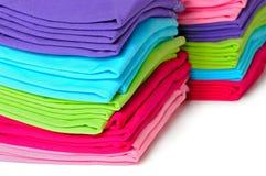 Mucchi delle magliette di donne colorate multi su fondo bianco Fotografie Stock