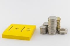 Mucchi delle monete e di una nota appiccicosa che dice 1+1 Fotografia Stock