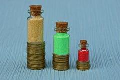 Mucchi delle monete gialle con le bottiglie di vetro della sabbia colorata Fotografia Stock