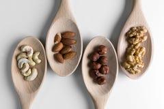 Mucchi delle noci, dei ceshews, della mandorla e delle nocciole negli spoones di legno su fondo bianco Dadi per salute Fuoco sele Fotografia Stock Libera da Diritti