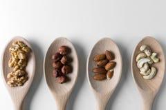 Mucchi delle noci, dei ceshews, della mandorla e delle nocciole negli spoones di legno su fondo bianco Dadi per salute Fuoco sele Immagine Stock Libera da Diritti