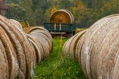 Mucchi di fieno del raccolto di autunno con il rimorchio con le balle di fieno fotografie stock