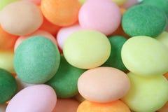 Mucchio alto chiuso delle caramelle rotonde di colore pastello, per fondo con il fuoco selettivo Immagini Stock