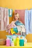 Mucchio biondo della tenuta della casalinga dei vestiti fotografia stock libera da diritti