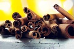 Mucchio dei bastoni di cannella su una priorità alta bianca di legno con la lampadina gialla Immagini Stock Libere da Diritti