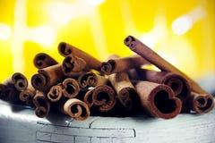Mucchio dei bastoni di cannella su una priorità alta bianca di legno con giallo Fotografie Stock Libere da Diritti