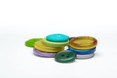 Mucchio dei bottoni di plastica di cucito variopinti su fondo bianco Immagini Stock