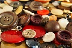 Mucchio dei bottoni variopinti indossati utilizzati sulla tavola di legno Fotografia Stock