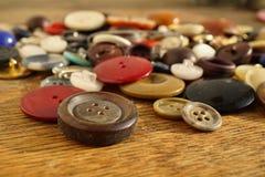 Mucchio dei bottoni variopinti indossati utilizzati sulla tavola di legno Immagine Stock