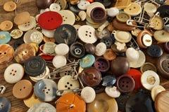 Mucchio dei bottoni variopinti indossati utilizzati sulla tavola di legno Fotografia Stock Libera da Diritti