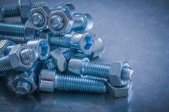 Mucchio dei bulloni e dei dadi sul conce metallico della costruzione del fondo Fotografia Stock