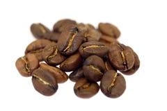 Mucchio dei chicchi di caffè marroni isolati su fondo bianco fotografia stock