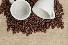 Mucchio dei chicchi di caffè su tela da imballaggio con due tazze Fotografia Stock Libera da Diritti