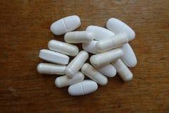 Mucchio dei confetti del citrato del calcio e delle capsule di citrato di magnesio su legno immagine stock libera da diritti