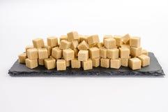 Mucchio dei cubi sucar della canna sul piatto scuro rettangolare dello scisto Fotografie Stock