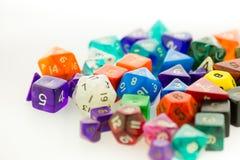 Mucchio dei dadi multicolori di gioco su una superficie bianca Immagine Stock