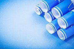 Mucchio dei disegni di costruzione sulla vista superiore del fondo blu Fotografie Stock