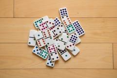 Mucchio dei domino sul pavimento di legno immagini stock