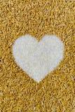 Mucchio dei granuli naturali del riso nella figura del cuore Fotografia Stock