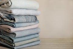 Mucchio dei jeans e dei maglioni tricottati dei vestiti, sciarpe, pullover Fotografia Stock Libera da Diritti