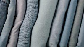 Mucchio dei jeans e dei maglioni tricottati dei vestiti, sciarpe, pullover Immagini Stock