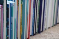 Mucchio dei libri che stanno in una fila Immagine Stock
