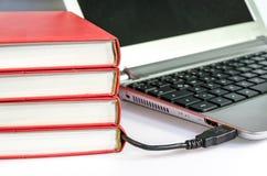 Mucchio dei libri collegati al computer portatile via USB fotografia stock libera da diritti