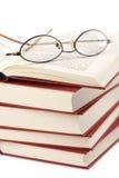 Mucchio dei libri con i vetri isolati Immagini Stock