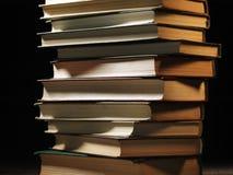 Mucchio dei libri dalla copertina rigida in una stanza oscura Immagine Stock