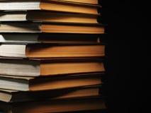 Mucchio dei libri dalla copertina rigida in una stanza oscura Fotografia Stock Libera da Diritti