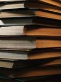 Mucchio dei libri dalla copertina rigida in una stanza oscura Fotografia Stock
