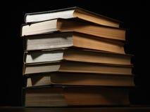 Mucchio dei libri dalla copertina rigida in una stanza oscura Immagini Stock Libere da Diritti
