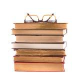 Mucchio dei libri e dei vetri isolati su fondo bianco accumulazione Fotografia Stock