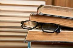 Mucchio dei libri e di vecchi vetri Immagini Stock