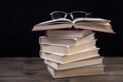 Mucchio dei libri e dei vetri Fotografia Stock