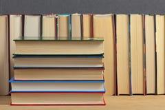 Mucchio dei libri su una superficie di legno Immagini Stock Libere da Diritti